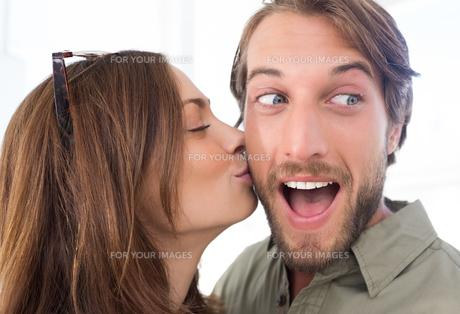 Woman kissing man with beard on the cheekの素材 [FYI00485409]