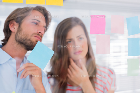 Two colleagues looking at sticky notesの写真素材 [FYI00485443]