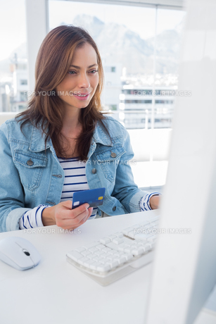 Smiling woman purchasing online with a credit cardの素材 [FYI00485450]