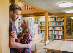 Young romantic couple with bookshelf at distance in libraryの写真素材 [FYI00485468]