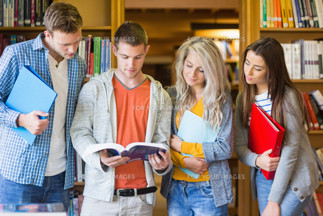 Students reading book against bookshelf in libraryの写真素材 [FYI00485471]