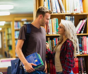 Smiling young couple against bookshelf in libraryの写真素材 [FYI00485472]