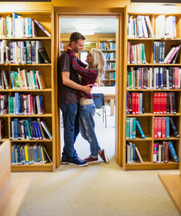 Romantic couple embracing by bookshelves in libraryの写真素材 [FYI00485474]