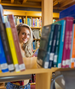 Smiling female amid bookshelves in the libraryの写真素材 [FYI00485477]