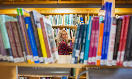 Smiling female amid bookshelves in the libraryの写真素材 [FYI00485482]