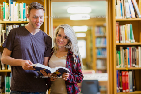 Portrait of two students reading book in the libraryの写真素材 [FYI00485489]