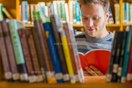 Student reading a book amid bookshelves in the libraryの写真素材 [FYI00485490]