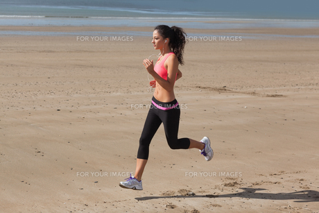 Full length of healthy woman jogging on beachの写真素材 [FYI00485499]
