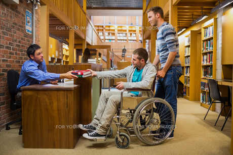 Male student in wheelchair at the library counterの素材 [FYI00485500]