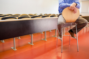 Low section of a teacher on chair in lecture hallの写真素材 [FYI00485501]
