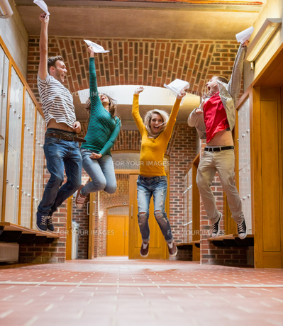 Group of students jumping in college corridorの素材 [FYI00485504]