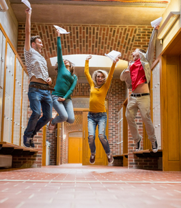 Group of students jumping in college corridorの写真素材 [FYI00485504]