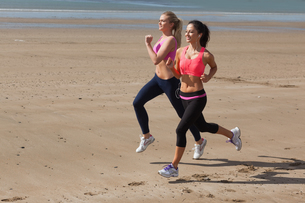 Full length of healthy women jogging on beachの写真素材 [FYI00485507]