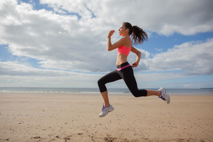 Full length of healthy woman jogging on beachの写真素材 [FYI00485508]