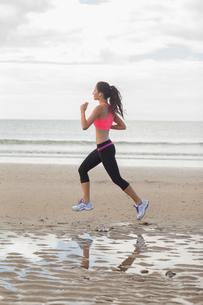 Full length of a healthy woman jogging on beachの写真素材 [FYI00485509]
