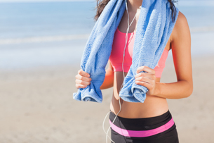Mid section of healthy woman with towel around neck on beachの写真素材 [FYI00485510]