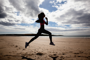 Full length of silhouette healthy woman jogging on beachの写真素材 [FYI00485512]