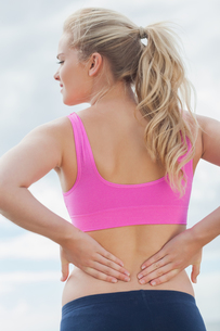 Rear view of healthy woman suffering from back pain on beachの写真素材 [FYI00485513]