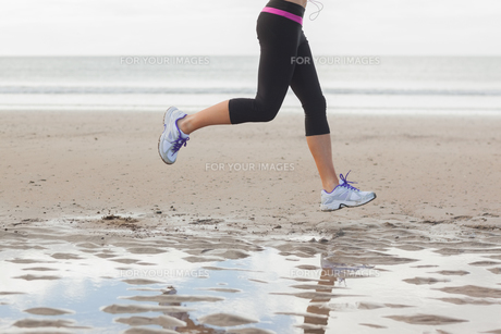 Low section of healthy woman jogging on beachの写真素材 [FYI00485514]