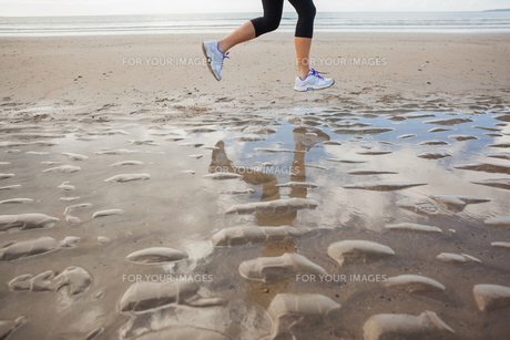 Low section of a healthy woman jogging on beachの写真素材 [FYI00485515]