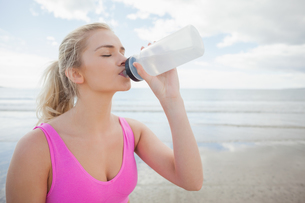 Beautiful healthy woman drinking water on beachの写真素材 [FYI00485516]
