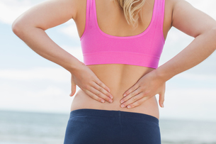 Mid section of toned woman from back pain on beachの写真素材 [FYI00485517]