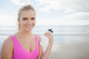 Smiling healthy woman with water bottle on beachの写真素材 [FYI00485518]