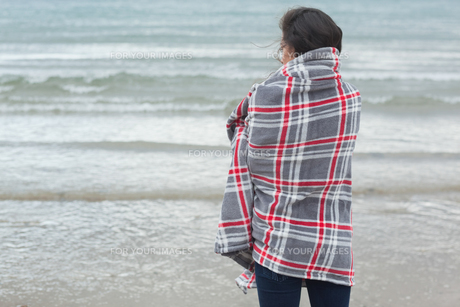 Rear view of woman covered with blanket looking at sea on beachの写真素材 [FYI00485519]