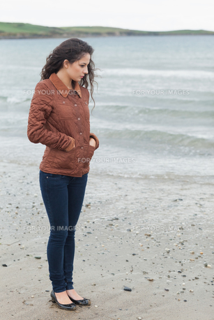 Cute young woman in stylish brown jacket on beachの写真素材 [FYI00485520]