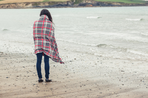 Rear view of woman covered with blanket looking at sea on beachの写真素材 [FYI00485523]
