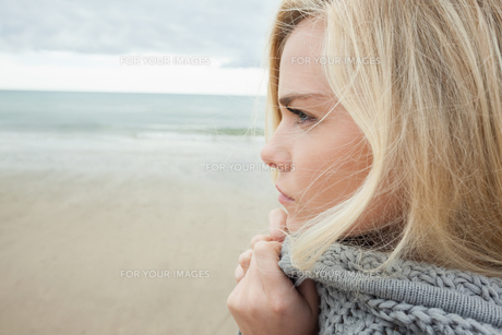 Cute young woman in gray knitted jacket on beachの写真素材 [FYI00485526]