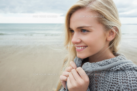 Cute smiling woman in gray knitted jacket on beachの写真素材 [FYI00485527]