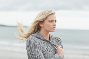 Cute young woman in gray knitted jacket on beachの写真素材 [FYI00485528]
