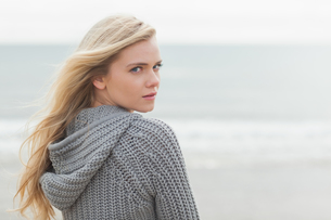Cute young woman in gray knitted jacket on beachの写真素材 [FYI00485532]
