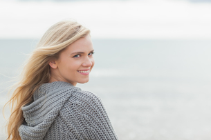 Cute young woman in gray knitted jacket on beachの写真素材 [FYI00485533]