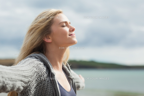 Side view of young woman stretching her arms on beachの写真素材 [FYI00485535]
