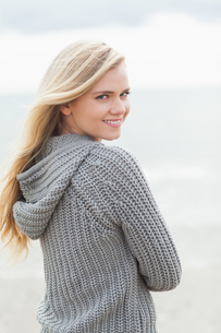 Cute young woman in gray knitted jacket on beachの写真素材 [FYI00485538]