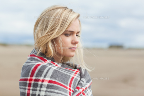 Side view of a woman covered with blanket at beachの写真素材 [FYI00485539]