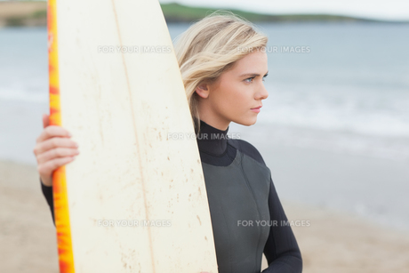 Beautiful young woman with surfboard on beachの素材 [FYI00485542]