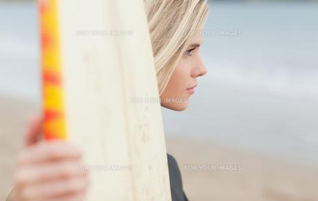 Beautiful woman with surfboard on beachの写真素材 [FYI00485543]