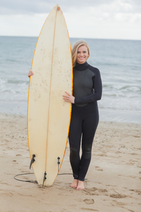 Smiling woman in wet suit holding surfboard at beachの素材 [FYI00485546]