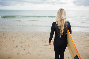 Rear view of woman in wet suit with surfboard at beachの写真素材 [FYI00485547]