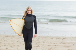 Smiling woman in wet suit holding surfboard at beachの素材 [FYI00485548]