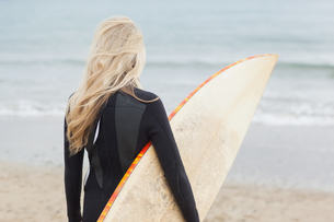 Rear view of woman in wet suit holding surfboard at beachの写真素材 [FYI00485549]