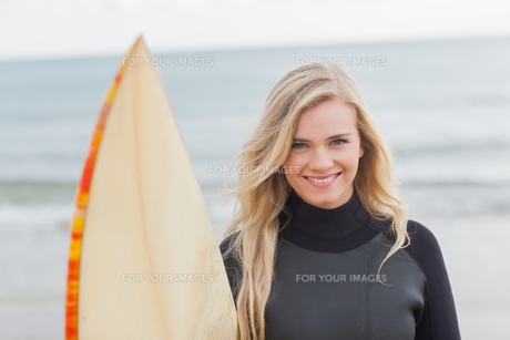 Smiling woman in wet suit holding surfboard at beachの素材 [FYI00485550]