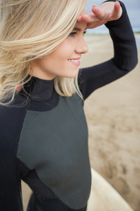 Side view of beautiful blond shielding eyes at beachの写真素材 [FYI00485554]