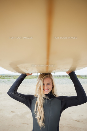 Smiling woman in wet suit holding surfboard over head at beachの素材 [FYI00485557]