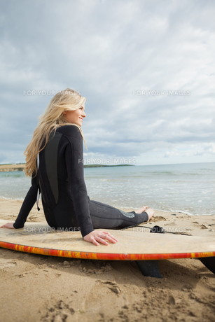 Smiling beautiful blond in wet suit with surfboard at beachの素材 [FYI00485559]
