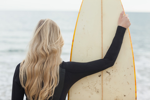 Rear view of a blond in wet suit with surfboard at beachの写真素材 [FYI00485560]