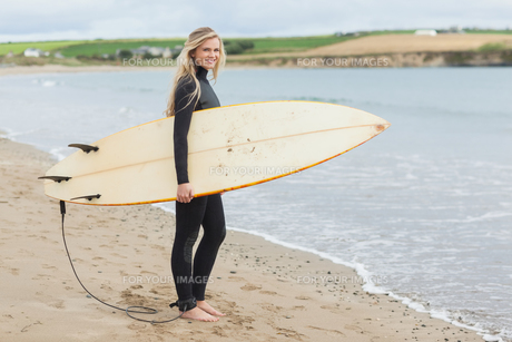 Beautiful woman in wet suit holding surfboard at beachの素材 [FYI00485561]